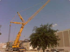 650 ton hydraulic Crane dismantling heavy equipment for salvage from the roof of the 3 story printing press after shutting down the plant.